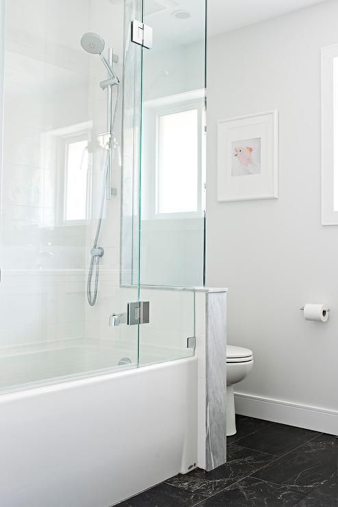 a minimalist bathroom with a black floor, a half wall that separates the toielt from the rest of the space, a shower-bathtub space