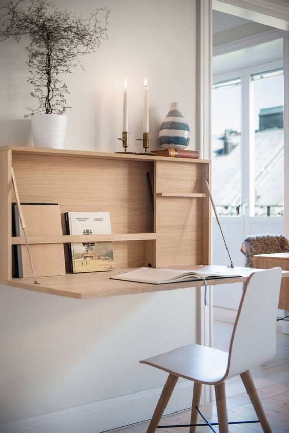 a minimalist wall-mounted desk with storage space inside, some candles and a desk surface that can be hidden