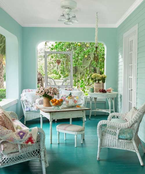 a minty and turquoise vintage sunroom with white wicker furniture, floral textiles, potted blooms and greenery
