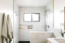 a modern bathroom with marble skinny tiles and black ones on the floor, a floating wooden vanity, a built-in niche for storage