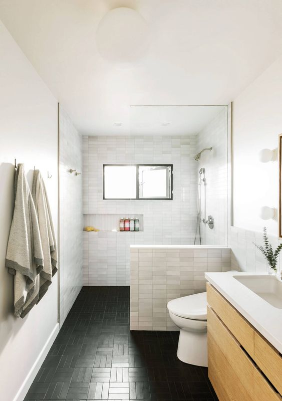 a modern bathroom with marble skinny tiles and black ones on the floor, a floating wooden vanity, a built in niche for storage