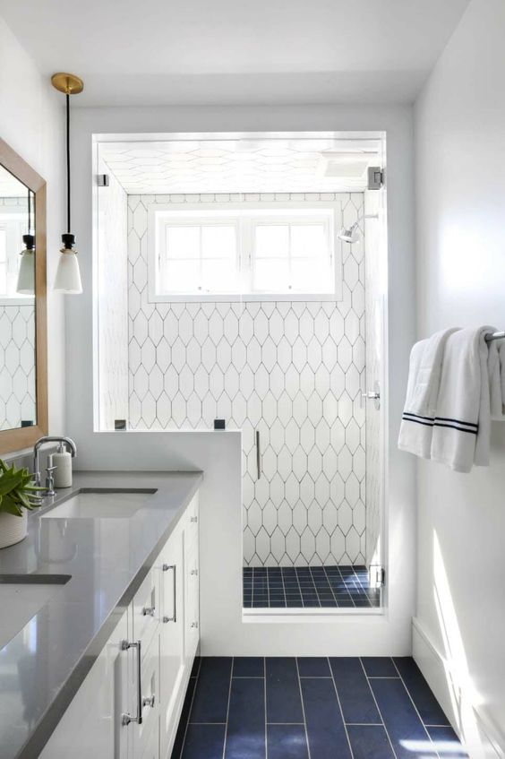 a modern coastal bathroom clad with navy and white tiles, a pony wall in the shower space and a white vanity