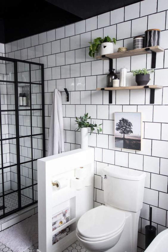 a modern neutral bathroom clad with white square tiles, with a French glass shower space, a pony wall to separate the toilet