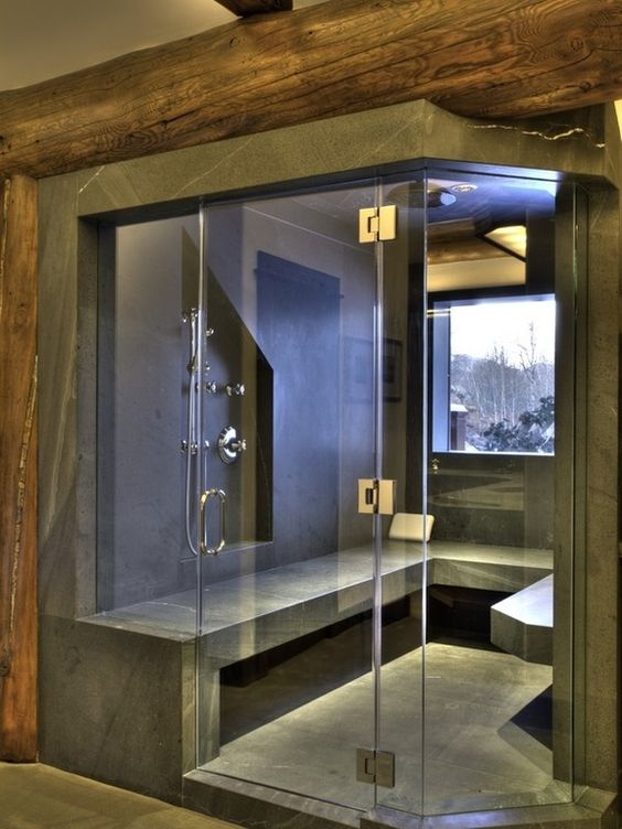 a modern steam room clad with grey stone, with a window and a long bench looks very edgy and bold