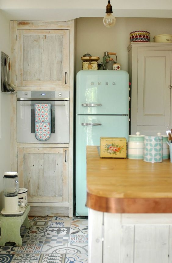 a neutral and pastel vintage kitchen with a blue fridge, a green bench, colorful mosaic tiles on the floor, a large kitchen island