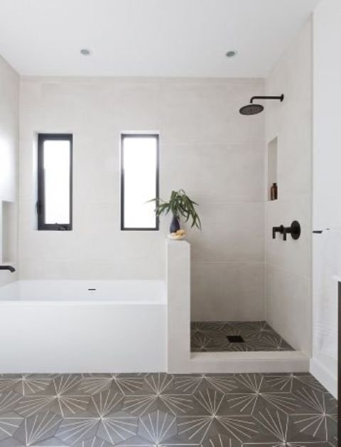 a neutral bathroom with mosaic tiles on the floor and neutral ones on the walls, a shower space with a pony wall that separates a shower and a bathtub