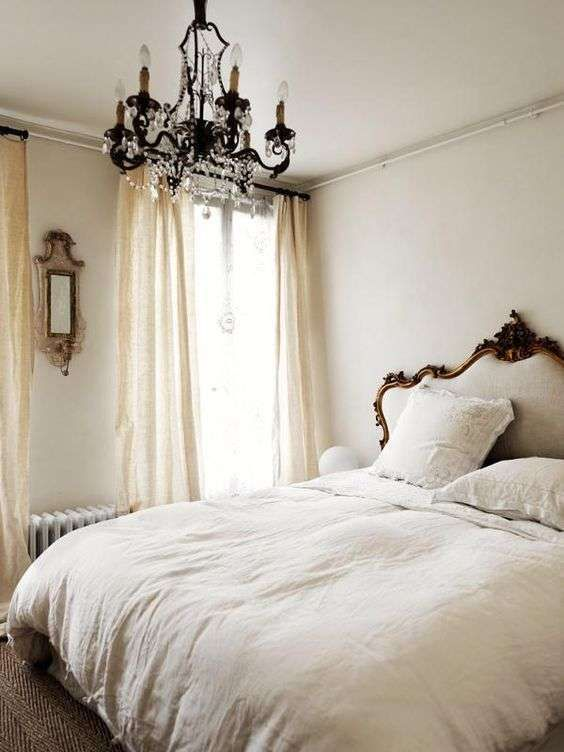 a neutral bedroom with printed textiles, a crystal chandelier, vintage furniture and beautiful framing