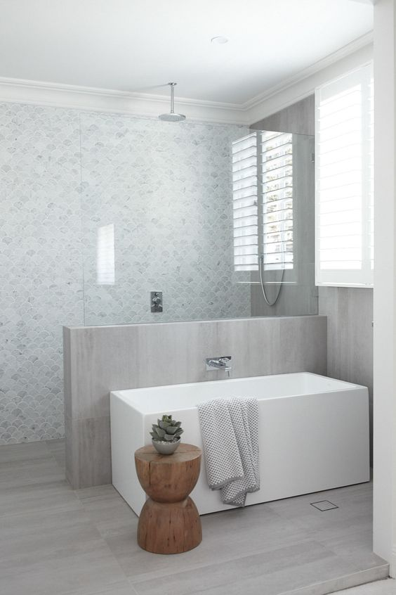 a neutral contemporary bathroom with marble fish scale tiles and a half wall covered with neutral wood plus the same on the floor