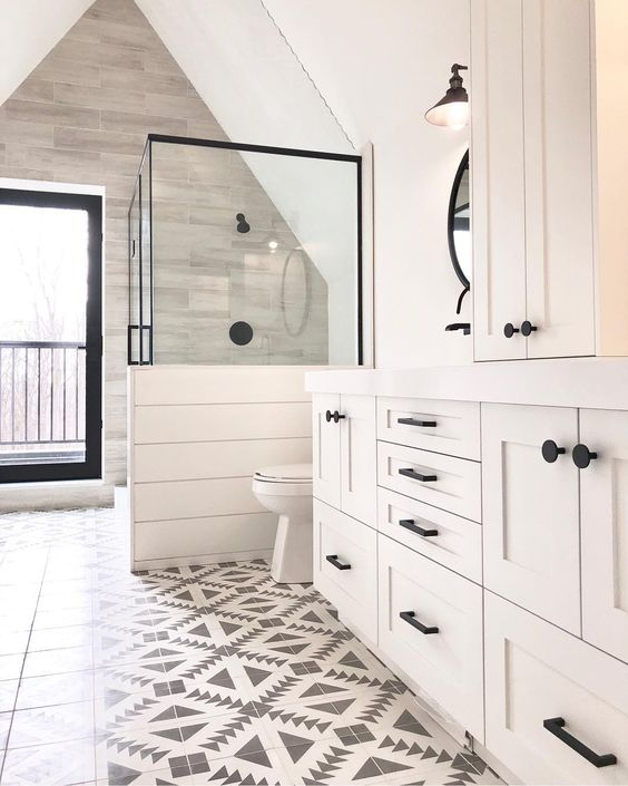 a neutral farmhouse bathroom with mosaic tiles, planked walls and cabinets, a shower space with a half wall