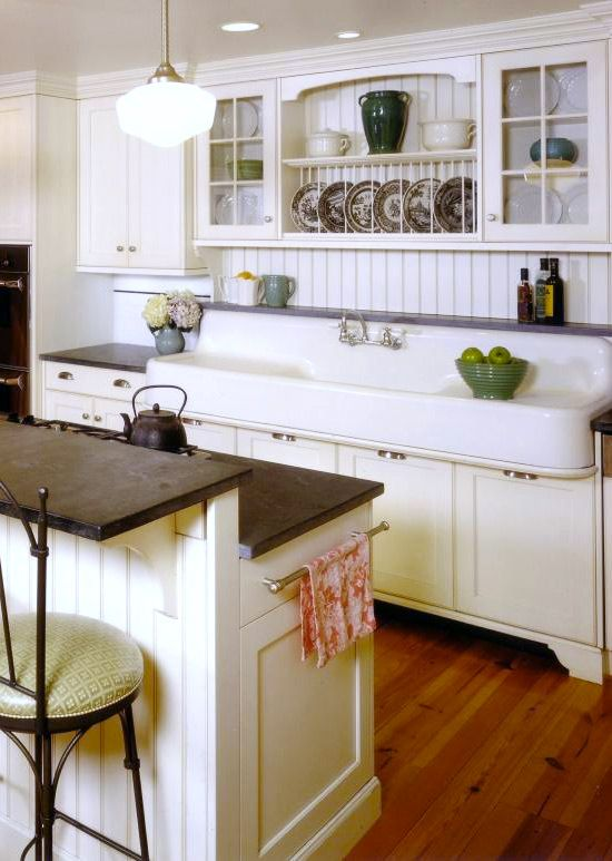 a neutral kitchen with white cabinets and a kitchen island, dark stained countertops, glass and usual cabinets and printed decor