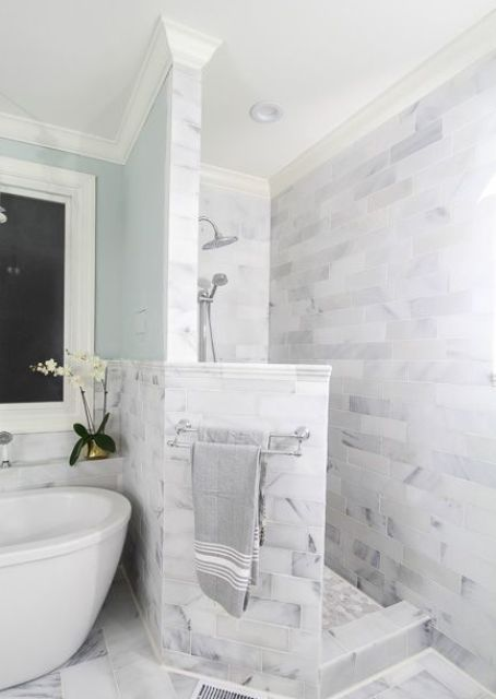 a neutral marble bathroom with a shower space with a pony wall, a bathtib and blue walls is very refined