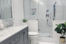 a neutral modern bathroom clad with marble hex tiles, with a shower space with half walls, a grey vnaity and a large mirror