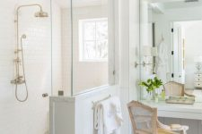 a neutral vintage bathroom with a shower space with a half wall, a vanity with a mirror and a vintage chair