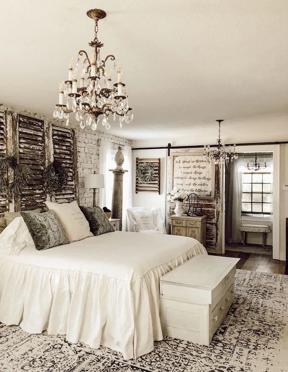 a neutral vintage bedroom with brick walls, shutters, a crystal chandelier and chic furniture plus artworks