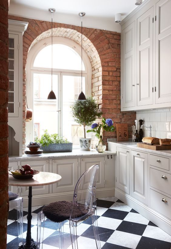 a neutral vintage kitchen with shaker style cabinets, a checked floor, potted greenery, pendant lamps and blooms, clear chairs and a round table