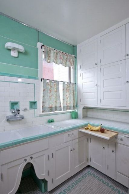 a neutral vintage kitchen with shaker style cabinets, bright turquoise touches and walls, floral curtains looks bright and very contrasting