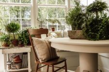 a neutral vintage sunroom with a stained chair, potted greenery and neutral textiles for a chic feel