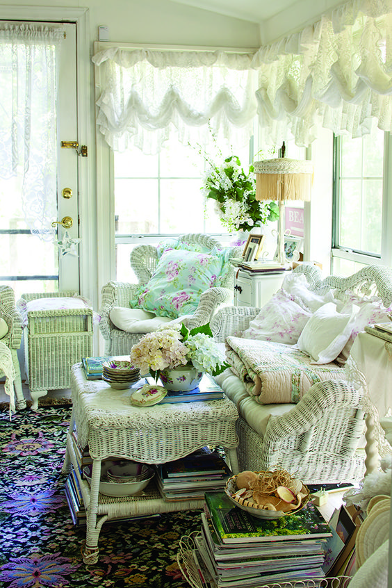 a neutral vintage sunroom with white wicker furniture, tulle ruffle curtains, floral textiles and a colorful rug