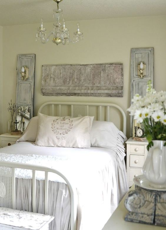 a pastel vintage bedroom with light green walls, a metal bed, neutral furniture, whitewashed decor and a fringe piece plus a crystal chandelier