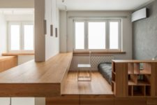 a plywood platform with drawers and shelves spearates the bedroom from the rest of the space, and an additional platform features a desk space