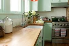 a pretty mint green kitchen with a white beadboard backsplash, butcherblock countertops, red pendant lamps and green knobs