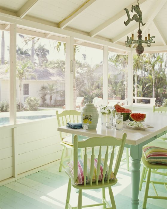 a pretty pastel cottage sunroom with pastel furniture, colorful textiles, a vintage chandelier and much sunshine is lovely