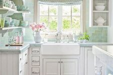 a pretty vintage cottage kitchen with white shaker style cabients, a green subway tile backsplash, open shelves and open cabinets and a printed curtain