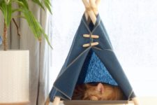 a raised cat teepee in navy is a cool space for your ufrry friend to sleep and to observe