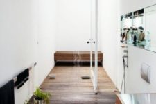 a raised wooden platform defines the shower space and a matching bench adds to the space