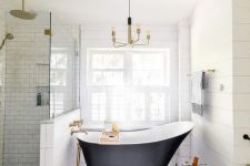 a refined farmhouse bathroom clad with hex and subway tiles, with a vintage bathtub, a stool with a plant and a vintage chandelier