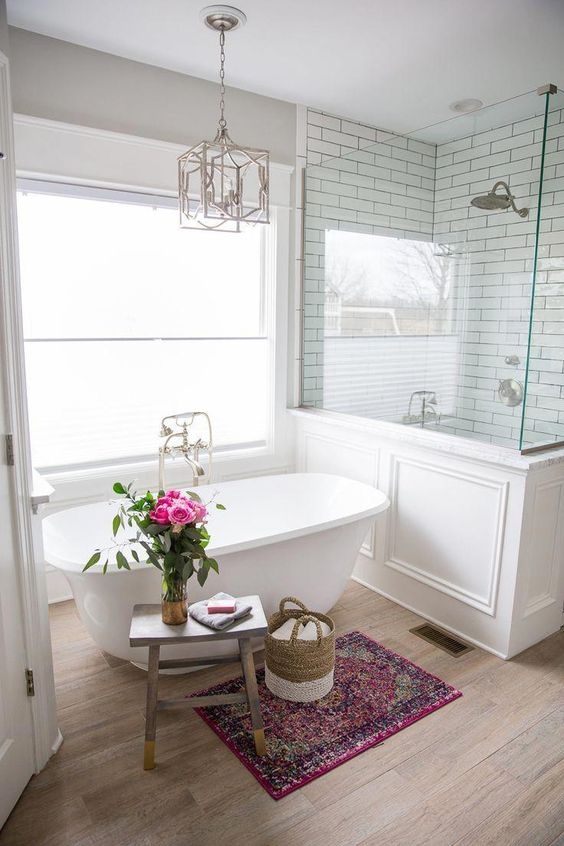 a refined farmhouse bathroom with a shower space with half walls, a small tub, a wooden stool and a chic chandelier