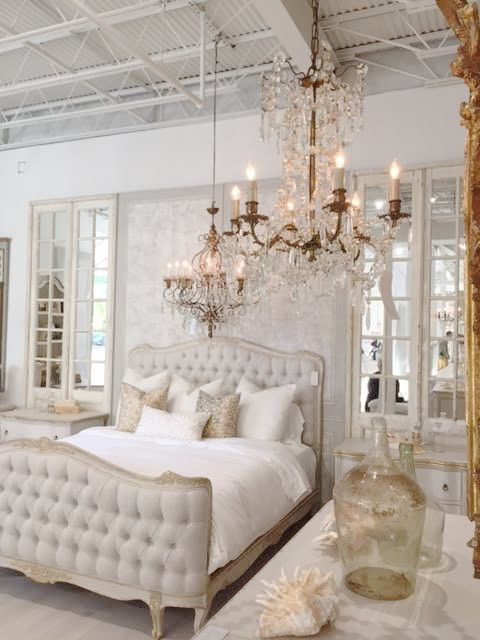 a refined neutral bedroom with a chic bed, crystal chandeliers, mirrors and printed pillows
