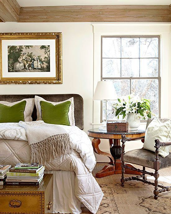 a refined vintage bedroom with a grey bed, heavy furniture, neutral bedding, green pillows, a vintage chest and blooms