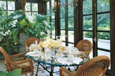 a refined vintage sunroom with a glass table and wicker chairs, a crystal chandelier with blooms and potted blooms and greenery