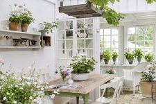 a refined vintage sunroom with white furniture – wicker and metal, a green table, potted greenery and blooms and hanging lamps