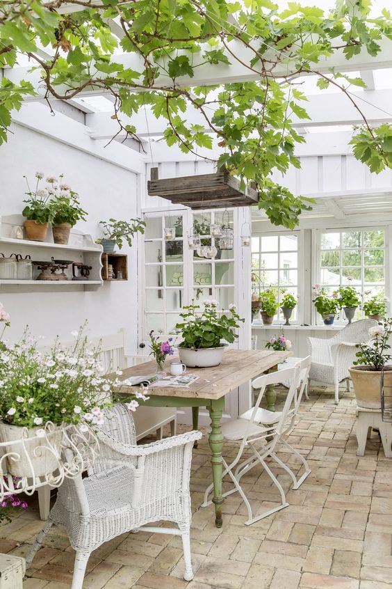 a refined vintage sunroom with white furniture - wicker and metal, a green table, potted greenery and blooms and hanging lamps