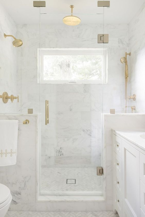a refined white marble bathroom with half walls int he shower space and touches of gold for a more chic look
