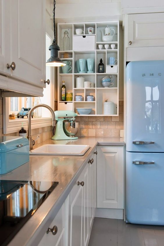 a retro kitchen with white shaker style cabinets, grey countertops, an open storage shelf, a blue fridge and blue and mint touches here and there