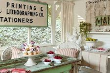 a romantic vintage sunroom in neutrals, with a grene table, neutral wicker chairs, bright textiles, shutters and neutral curtains