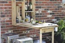 a rustic outdoor bar styled as a Murphy table is a geat idea for a small outdoor space to refresh yourself