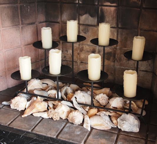 a seaside style fireplace filled with seashells and with a modern candelabra with pillar candles
