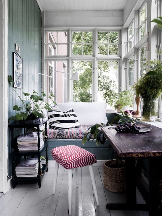 a small and cute vintage sunroom with a built-in bench, dark furniture, potted greenery and a basket