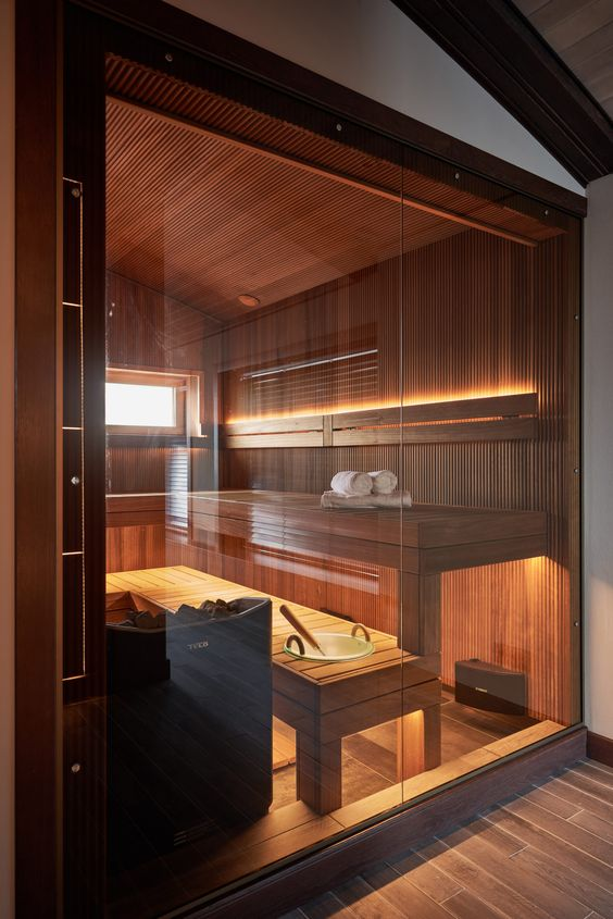 a small but gorgeous sauna done with two benches, clad with wood and built-in lights