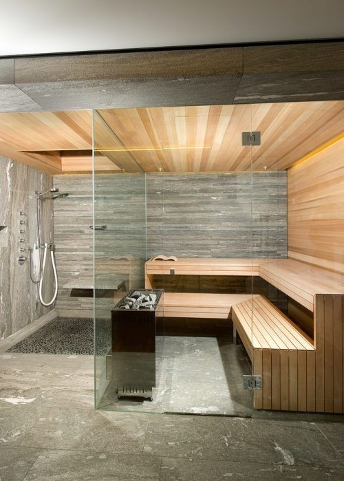 a small but very chic steam room clad with wood - light-stained and weathered and tiles plus built-in lights and glass walls