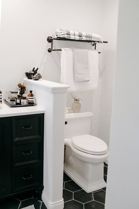 a small farmhouse bathroom clad with black hex tiles on the floor, with a half wall to separate the toilet and a black vanity