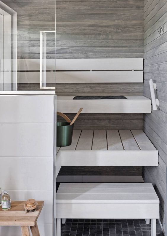 a small minimalist steam room clad with weathered wood and with whitewashed benches