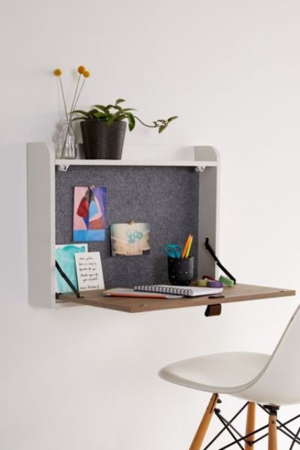 a small storage space with a foldable desk surface, some plants and felt inside the box is a cool idea