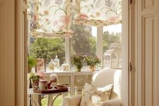 a small vintage sunroom with neutral furniture, floral printed shades and pillows, potted blooms and greenery
