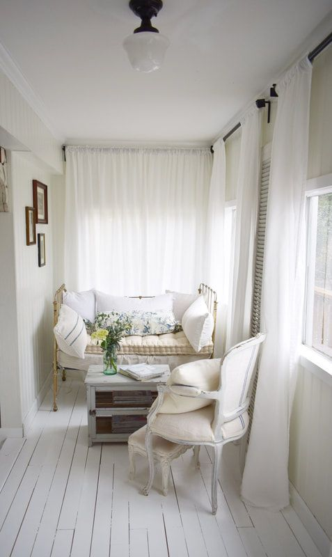 a small white vintage sunroom with a forged daybed and a wooden chair, neutral textiles and a gallery wall