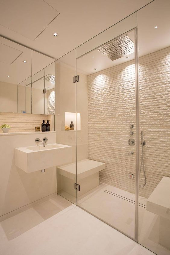a small yet chic white steam room with a stone wall and mini benches plus built-in lights is cool